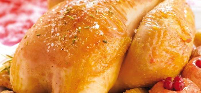 Roast Label Rouge traditional capon with baked apples and potatoes